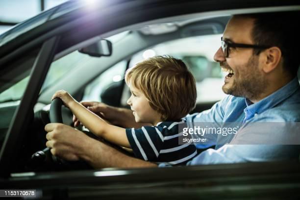 ショールームで新車をテストする幸せな父と息子。 - 試運転 ストックフォトと画像