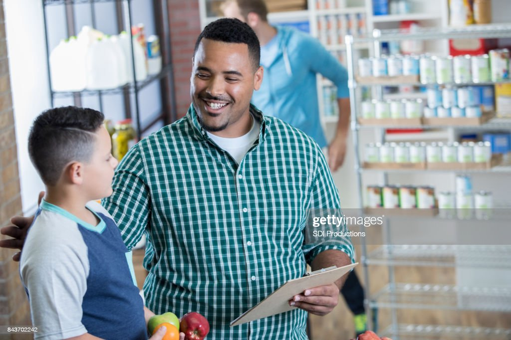 Happy father and son volunteer in local food bank : Stock Photo