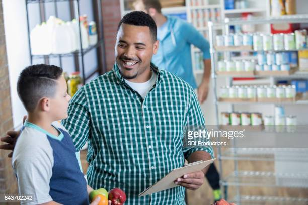 Happy father and son volunteer in local food bank