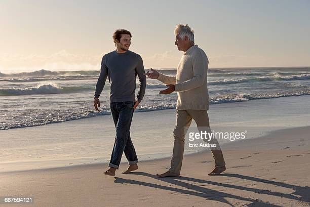 Happy father and son walking on the beach