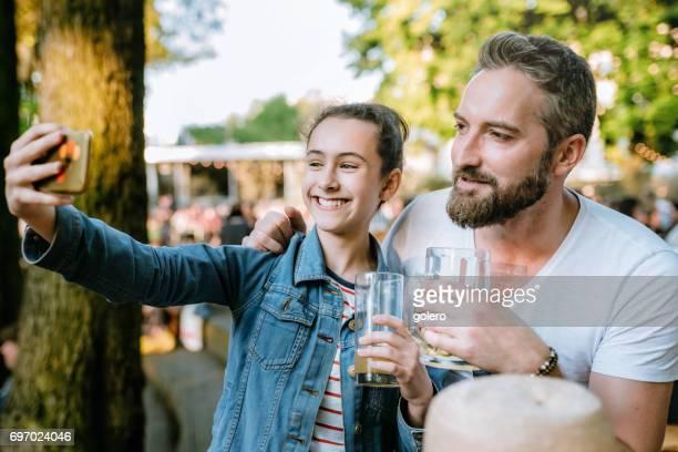 feliz padre e hija adolescente toma selfie en jardín de la cerveza