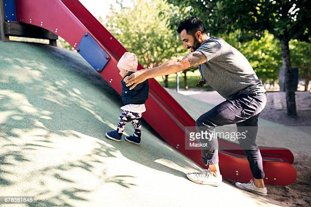 Happy father assisting daughter in climbing steep by slide at park
