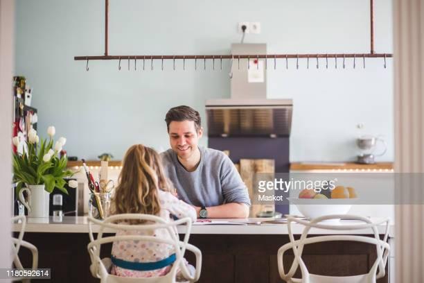 happy father assisting daughter studying in kitchen at home - alleenstaande vader stockfoto's en -beelden