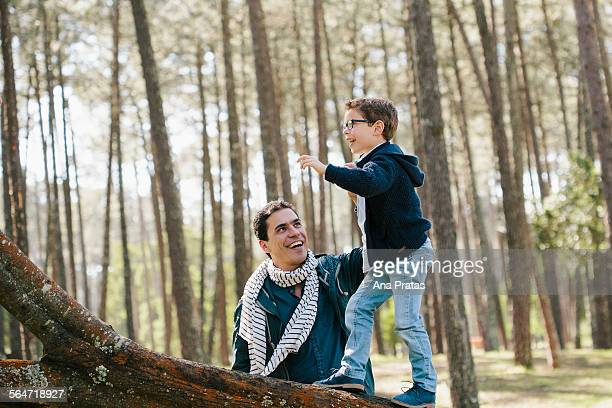 Happy father assisting son in climbing tree at forest