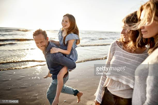 happy father carrying daughter piggyback by the sea - travel stock-fotos und bilder