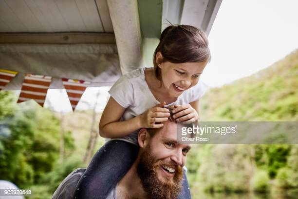 Happy father carrying daughter piggyback on a houseboat