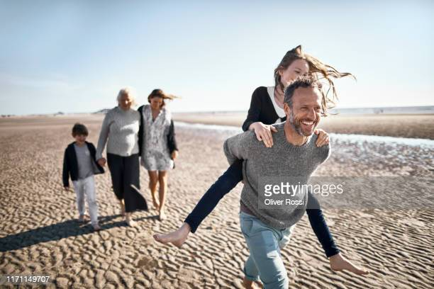 happy father carrying daughter piggyback on the beach - carefree stock pictures, royalty-free photos & images