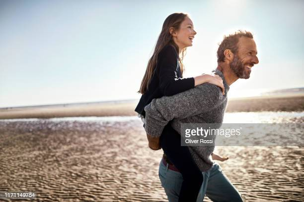happy father carrying daughter piggyback on the beach - piggyback stock pictures, royalty-free photos & images
