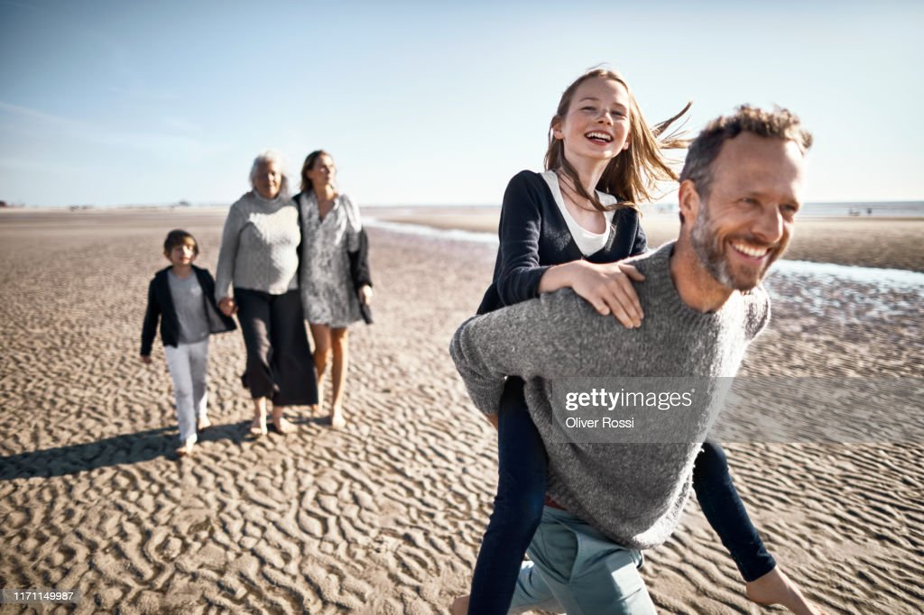 Happy father carrying daughter piggyback on the beach : Stock Photo