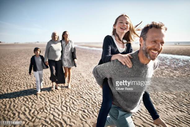 happy father carrying daughter piggyback on the beach - vitaliteit stockfoto's en -beelden