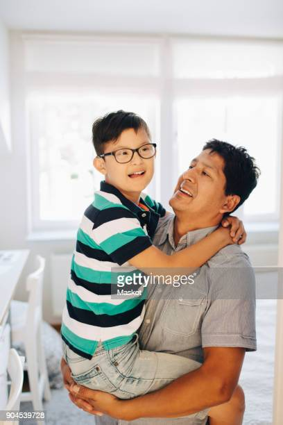 Happy father carrying disabled son while standing at home