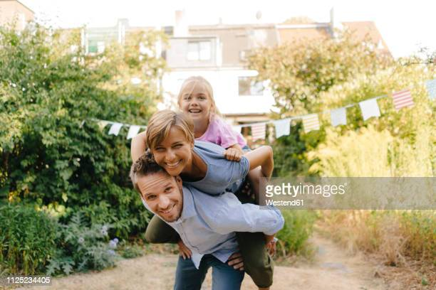 happy father carrying family piggyback in garden - enthousiaste photos et images de collection