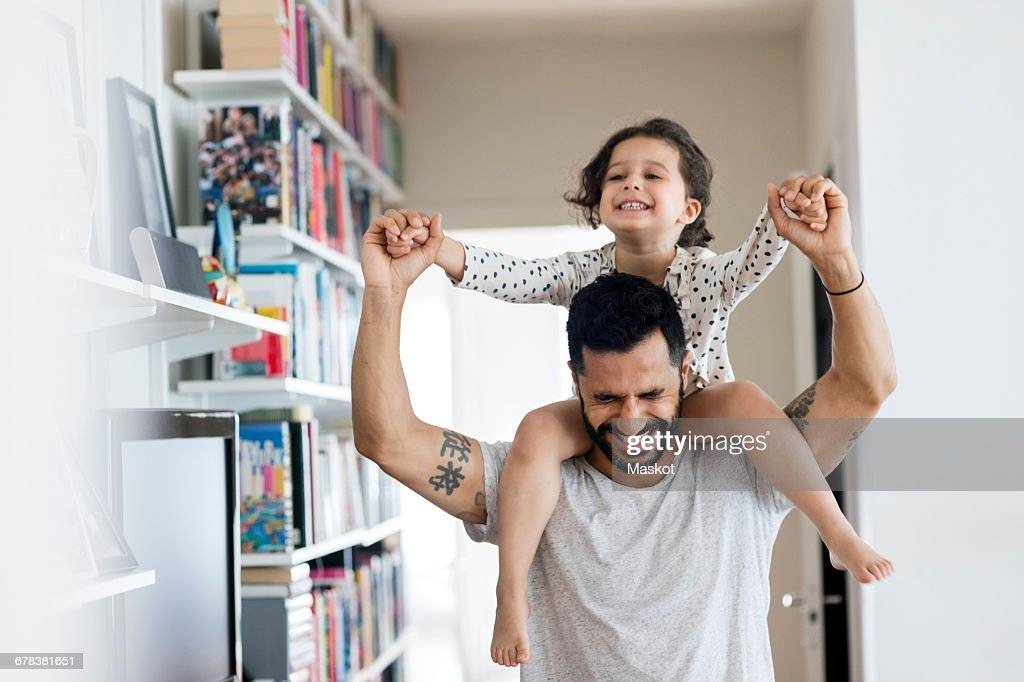 Happy father carrying girl on shoulder while standing at home : Stock Photo