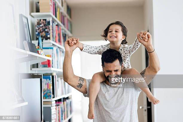happy father carrying girl on shoulder while standing at home - giochi per bambini foto e immagini stock