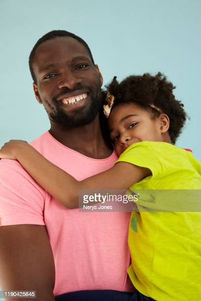 happy father carrying his daughter against a pale blue background - nerys jones stock photos and pictures