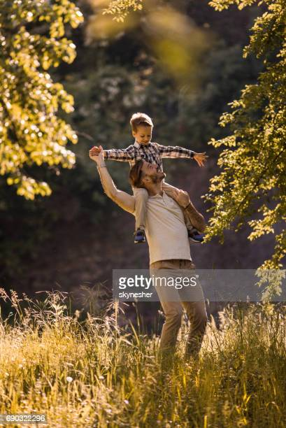 Happy father carrying his son on shoulders and having fun with him in the park.