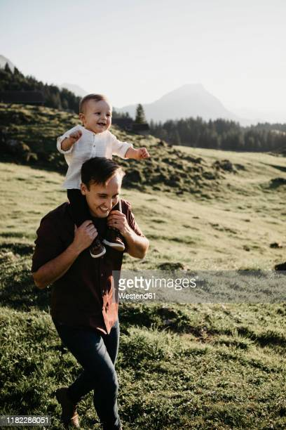 happy father carrying little son on shoulders on a hiking trip, schwaegalp, nesslau, switzerland - genderblend stock pictures, royalty-free photos & images