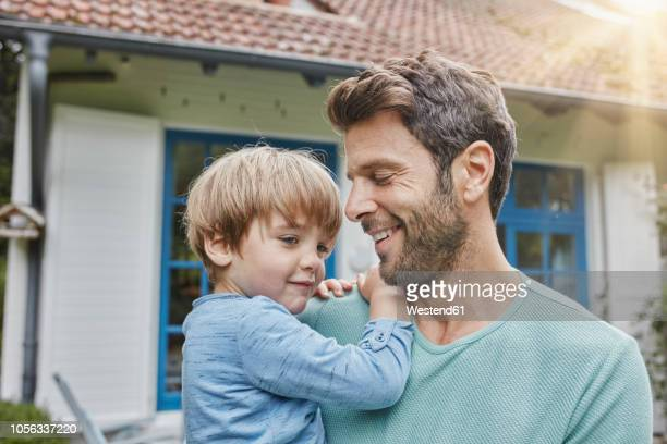 happy father carrying son in front of their home - vater stock-fotos und bilder