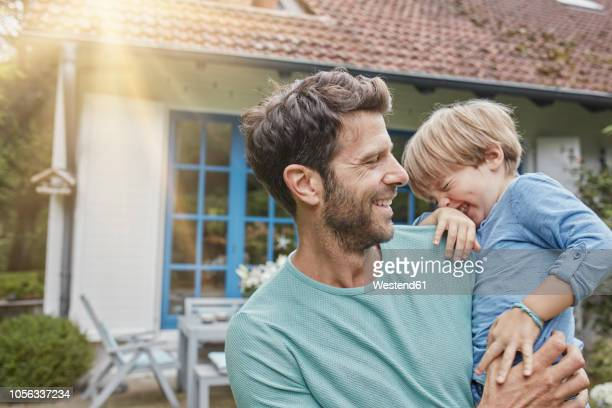 happy father carrying son in front of their home - outdoors stock-fotos und bilder