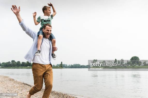 happy father carrying son on shoulders at the riverside - carrying on shoulders stock pictures, royalty-free photos & images
