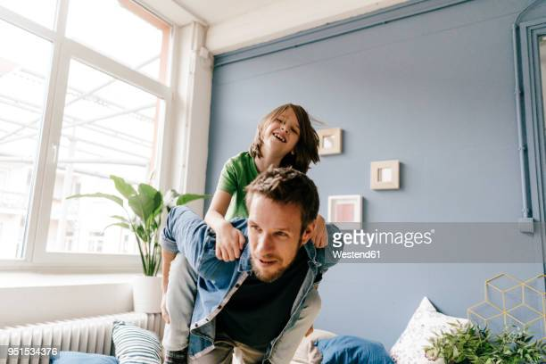 happy father carrying son piggyback at home - piggyback stock pictures, royalty-free photos & images