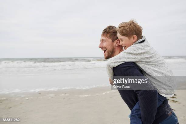 Happy father carrying son piggyback on the beach