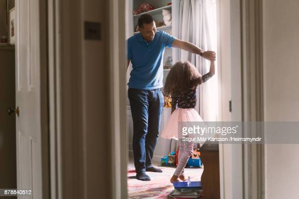 Happy father dancing with daughter in bedroom
