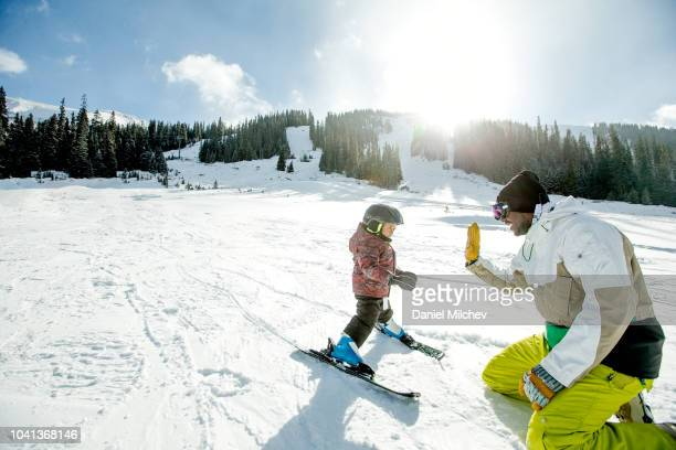happy father giving high five to his young boy as he is teaching him how to ski during the winter. - family and happiness and diverse stock photos and pictures