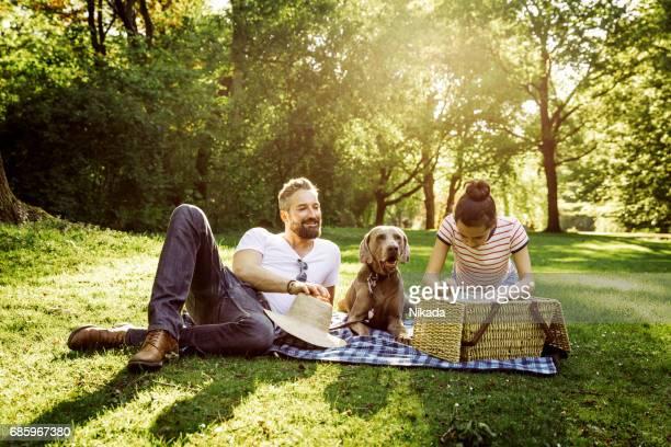 glücklicher Vater mit einem Picknick mit Teenager-Tochter und Hund