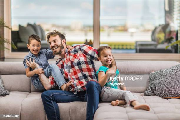 happy father having fun while playing with his small kids in the living room. - penthouse girls stock pictures, royalty-free photos & images
