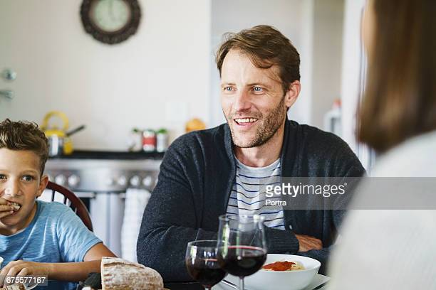 Happy father having meal with son at home