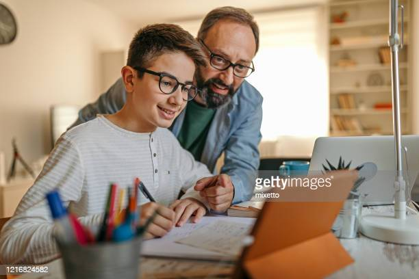 happy father helping son with homework - pre adolescent child stock pictures, royalty-free photos & images