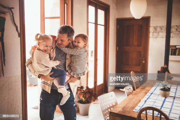 happy father holding little daughters in his arms at home - returning stock pictures, royalty-free photos & images