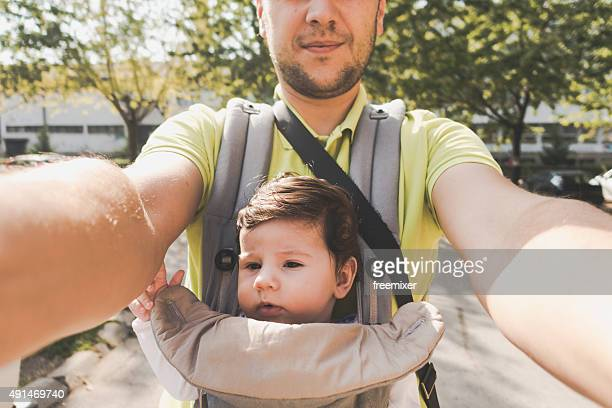Happy father holds his baby boy in a baby carrier