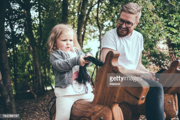 Happy father looking at daughter riding wooden horse in park