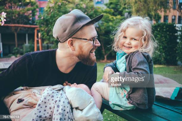 Happy father looking at daughter while holding son in park
