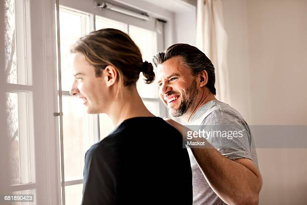 Happy father looking at son while standing by door at new home