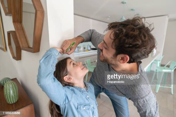 happy father measuring daughter against the walll while she cheats with her height both smiling - high up stock pictures, royalty-free photos & images