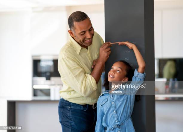 happy father measuring his daughter at home - medir imagens e fotografias de stock