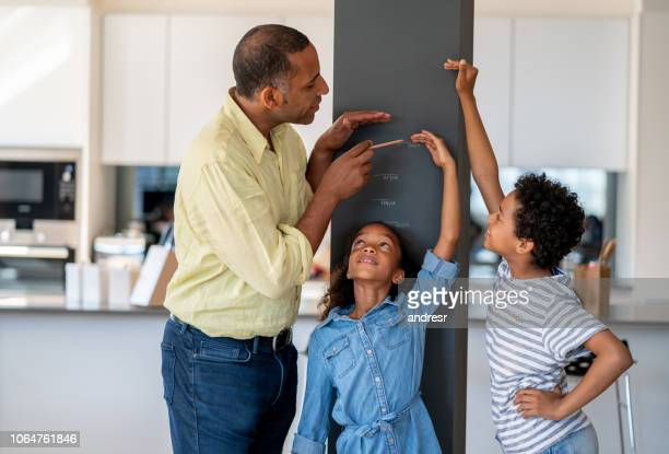 happy father measuring his kids at home - medir imagens e fotografias de stock