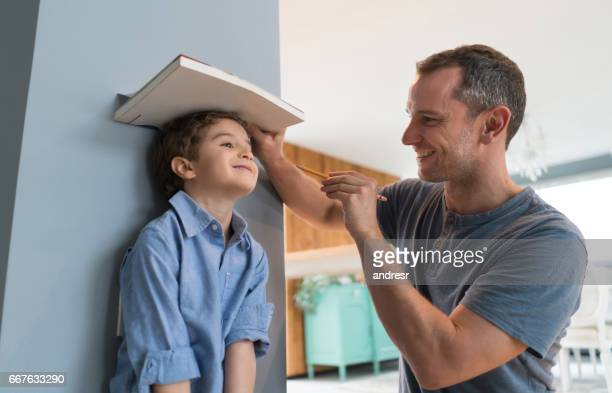 happy father measuring his son at home - medir imagens e fotografias de stock