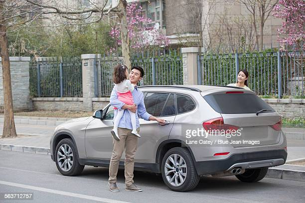 Happy father opening car door with daughter in his arms