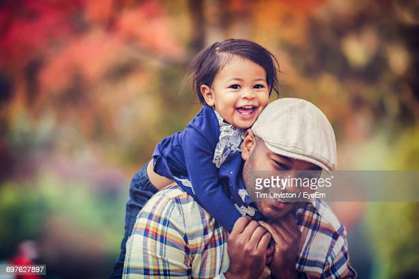 Happy Father Piggybacking Daughter During Autumn