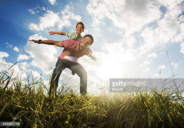 Happy father piggybacking his son against the sky.