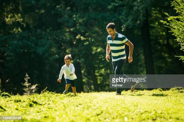 glücklicher vater spielt fang mit seinem sohn im freien - kemter stock-fotos und bilder