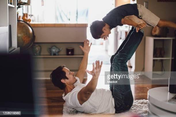 happy father playing while holding son in mid-air on legs - stay at home father stock pictures, royalty-free photos & images