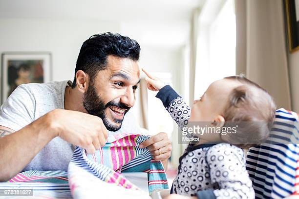 Happy father playing with baby girl at home