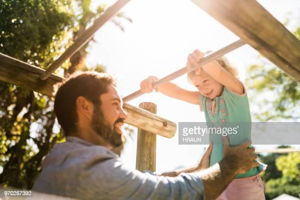 幸せな父娘とジャングルジムで遊んで - ジャングルジム ストックフォトと画像