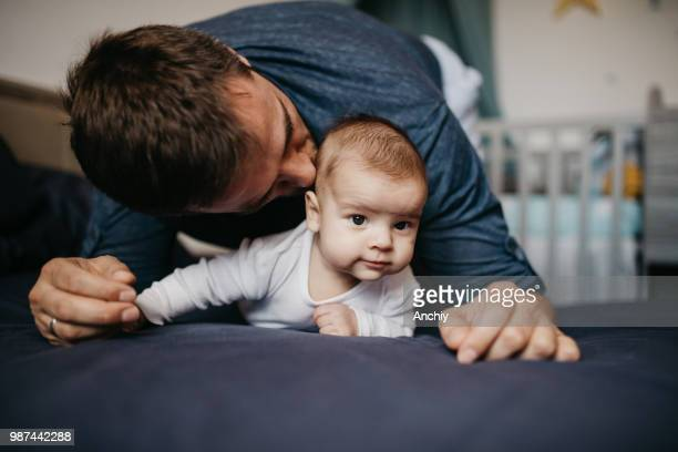 Happy father playing with his baby boy