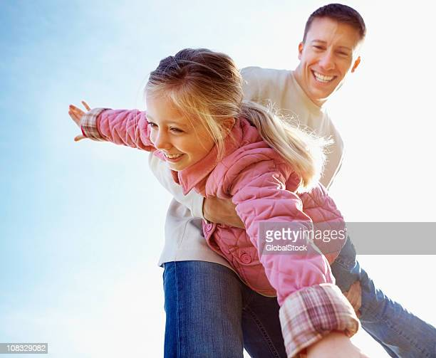 Happy father playing with his daughter against clear sky